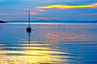 Blue and gold sailboat on bay